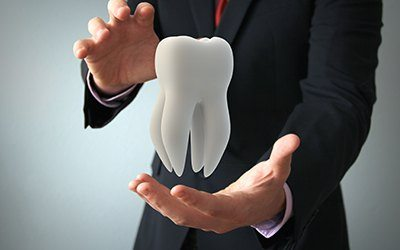 business man holding tooth