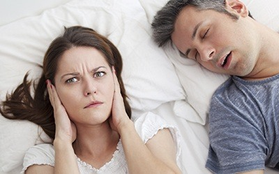 Woman covering ears in bed next to snoring man