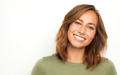 A woman smiling in front of a white background